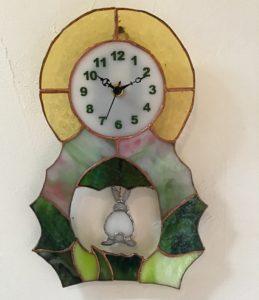 ステンドグラスの振り子時計です。ウサギが巣穴に戻って行く様子